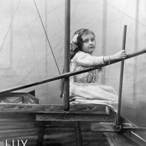 Une petite fille dans un avion factice. Photo prise en studio à Paris en 1910.